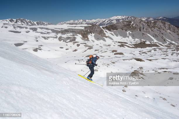 man skiing on snow covered mountain - andrea rizzi stock pictures, royalty-free photos & images