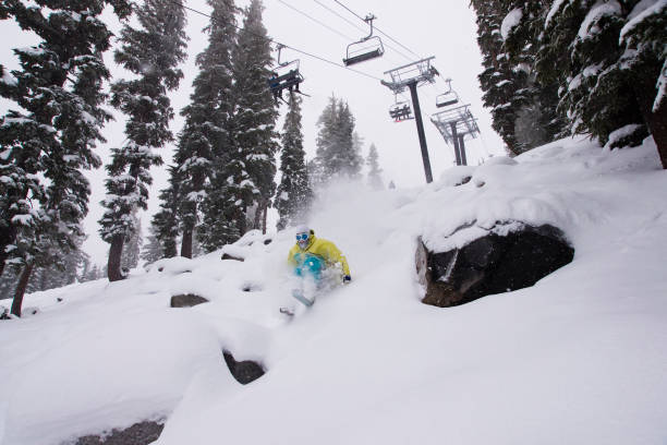 A man skiing powder snow beneath a chairlift at Northstar at Tahoe in California