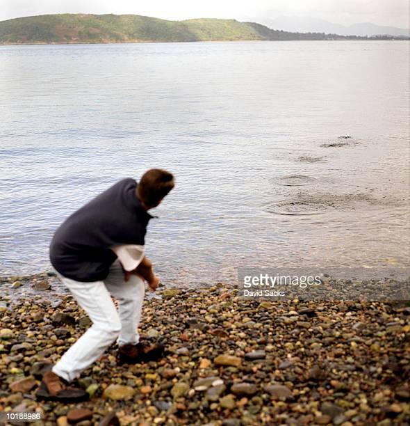 Man skipping stone in lake, Scotland