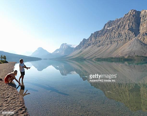 Man skips stone across Bow Lake, beside woman