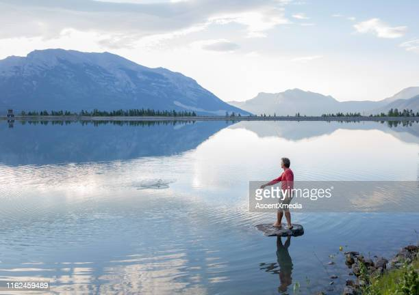 man skips stone along mountain lake in the morning - reflection pool stock pictures, royalty-free photos & images