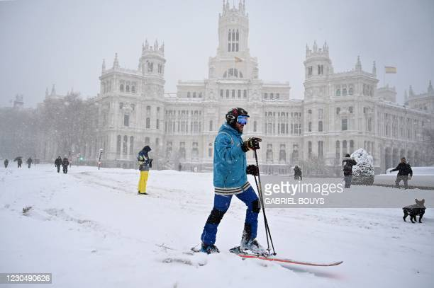 Man skis in Cibeles square amid a heavy snowfall in Madrid on January 9, 2021. - Heavy snow fell across much of Spain, leaving huge areas blanketed...