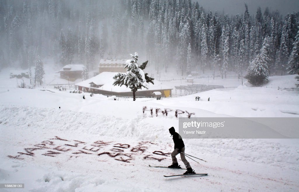 A man skis next to a New Year's greeting written in the snow on December 31, 2012 in Gulmarg, to the west of Srinagar, the summer capital of Indian-administered Kashmir, India. Following the second round of heavy snowfall in Kashmir valley, skiers from around the globe have reached the famous ski resort of Gulmarg, located less than six miles from the ceasefire line - or Line of Control (LoC) - that divides Kashmir from India and Pakistan. The resort is known for long-run skiing, snow-boarding, heli-skiing and steep mountains. A number of foreign governments, including the United Kingdom, have lifted travel advisories to citizens traveling to Kashmir which has raised the hopes of the local tourism industry following violence in the region.
