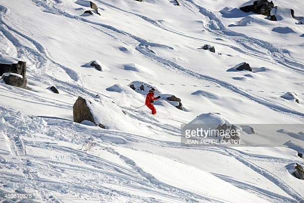 A man skis on December 31 2013 in the French Alps ski resort of Meribel next to the rocky part between two slopes where German retired Formula One...