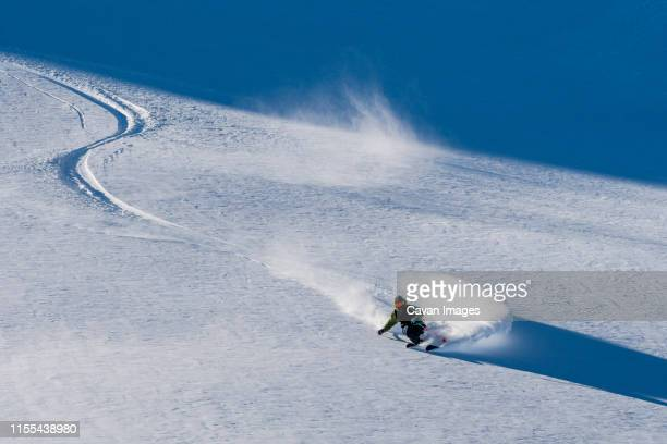 a man skis powder on a sunny bluebird day in copahue, argentina. - back country skiing stock pictures, royalty-free photos & images