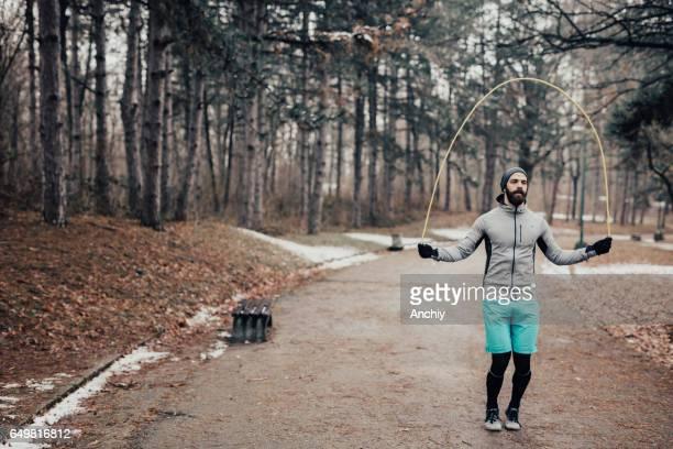 Skpping homme de corde dans le parc pendant la saison d'hiver