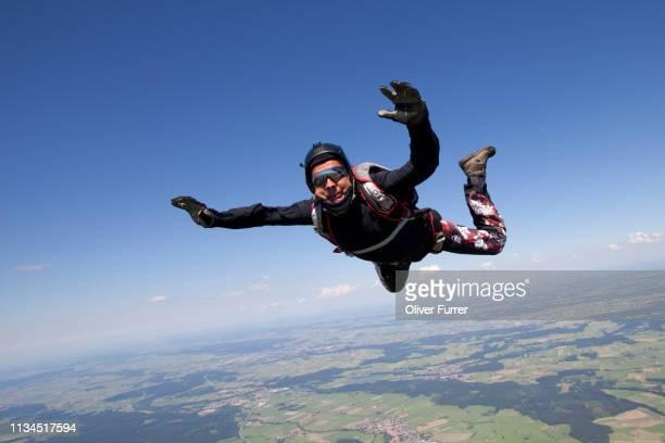 man skydiving over rural landscape - スカイダイビング ストックフォトと画像