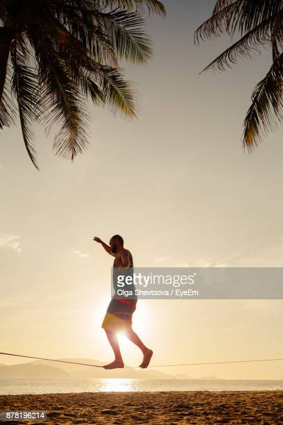 Man Slacklining On Rope At Beach Against Sky During Sunset