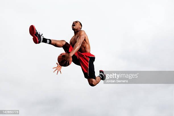 Man slam dunking a basketball.