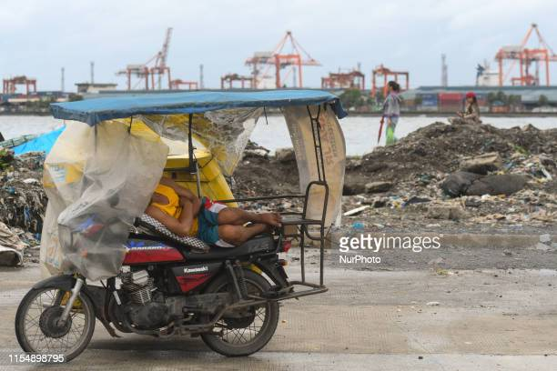 A man sleep on his tricycle on a cost road in Baseco Compound The Batangas Shipping and Engineering Company Compound is the largest among five...