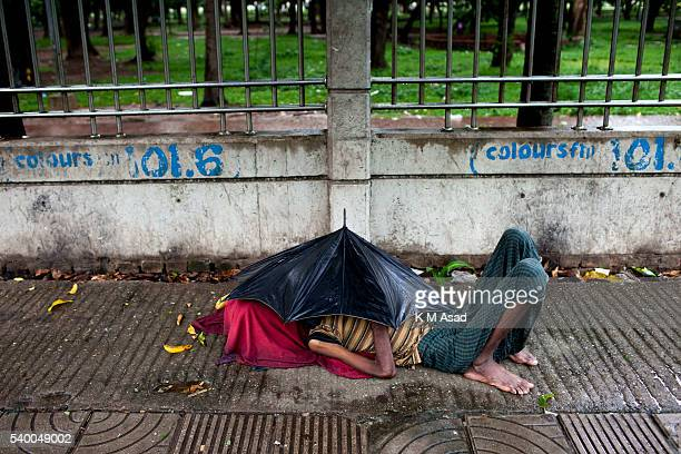 OLD DHAKA DHAKA BANGLADESH A man sleep under the umbrella in the side of the street during a rainy day the first day of Ramadan in Dhaka Bangladesh...