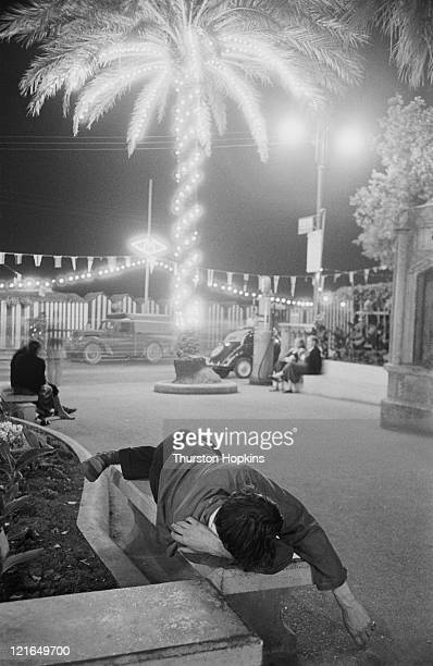 A man sleeping an a wall at night on Paraggi Beach near the tourist resort of Portofino Italy August 1952 Original Publication Picture Post 6023 unpub