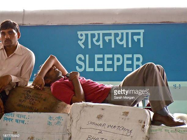 Man sleeping at Old Delhi railway station. The man is sleeping on front of some cargo whilst behind him is a sign on a train saying 'sleeper'. The...