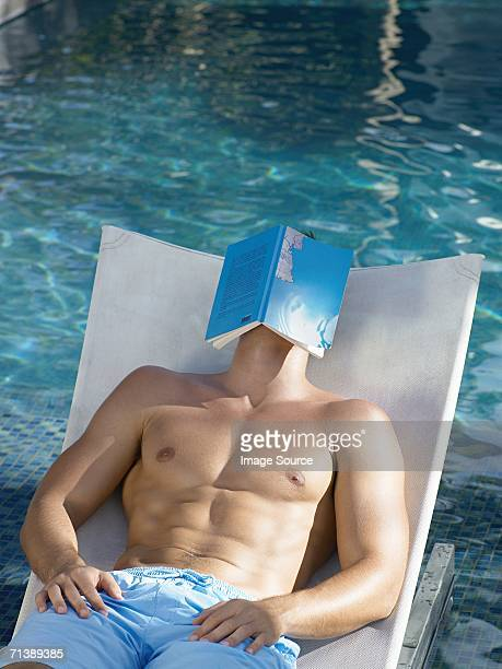 man sleeping by swimming pool - zwembroek stockfoto's en -beelden