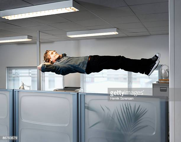 man sleeping floating above his office table. - in de lucht zwevend stockfoto's en -beelden