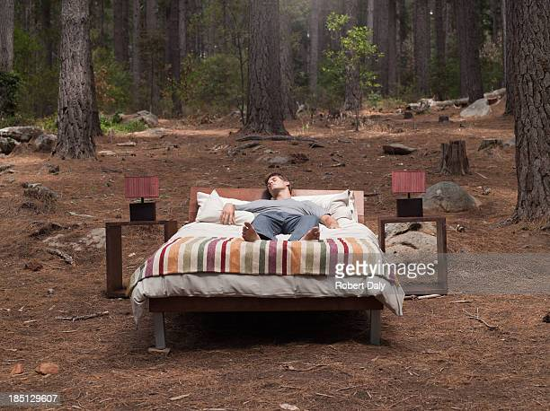 A man sleeping in a bed outdoors in the woods