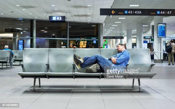 Man sleeping in an airport.