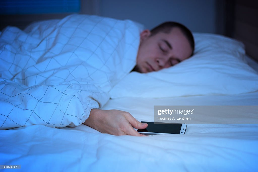 Man sleeping in bed and holding a mobile phone : Stock Photo