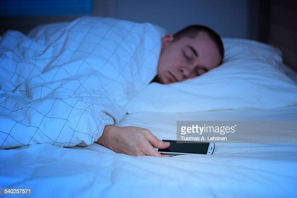 Man sleeping in bed and holding a mobile phone