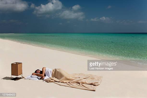 Man sleeping in bed on beach