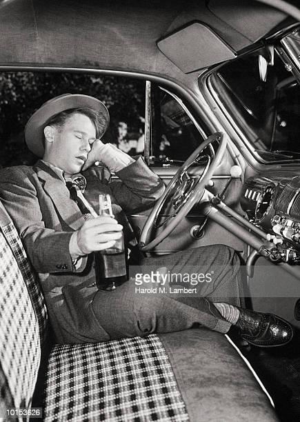 Man sleeping in car, holding liquor bottle (B&W)