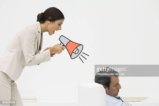 Man sleeping in chair, woman standing behind him, shouting into megaphone