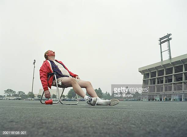 man sleeping in folding chair in stadium parking lot - drunk stock pictures, royalty-free photos & images