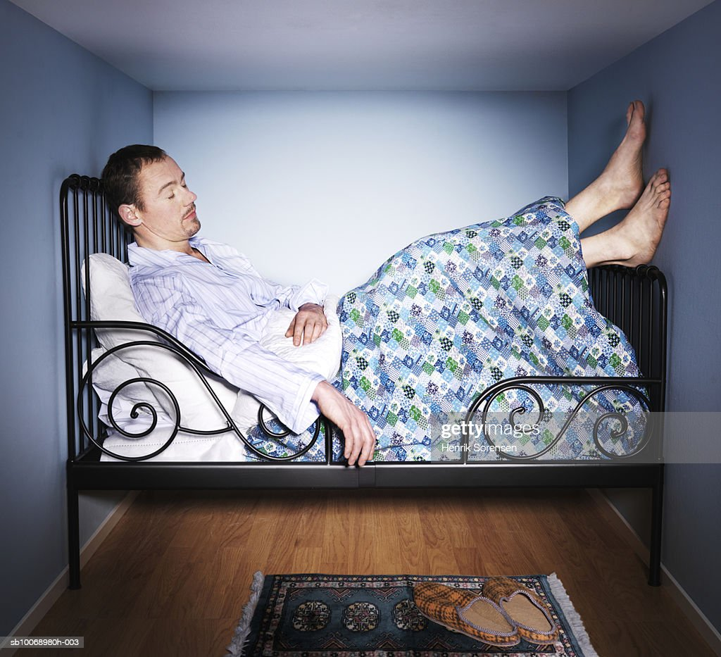 Man sleeping in small bed room, side view : ストックフォト