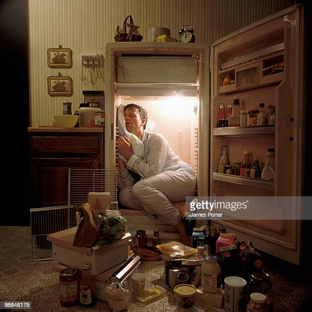 man sleeping inside refrigerator - dormir humour photos et images de collection