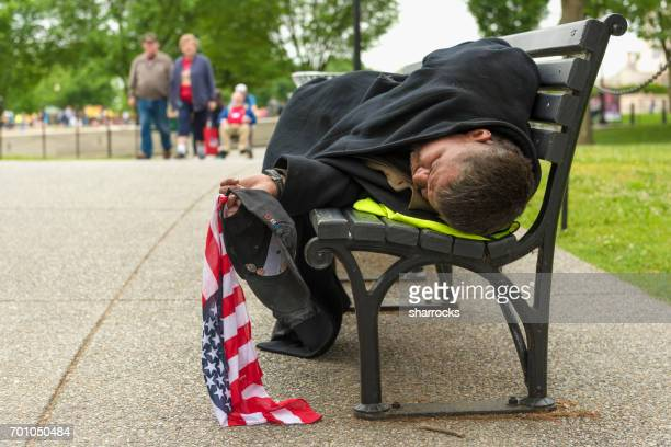 man sleeping on a park bench in washington dc whilst holding a stars and stripes flag - homeless veterans stock photos and pictures