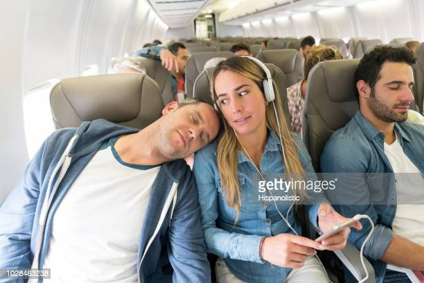man sleeping on a passenger's shoulder in an airplane - passenger stock pictures, royalty-free photos & images