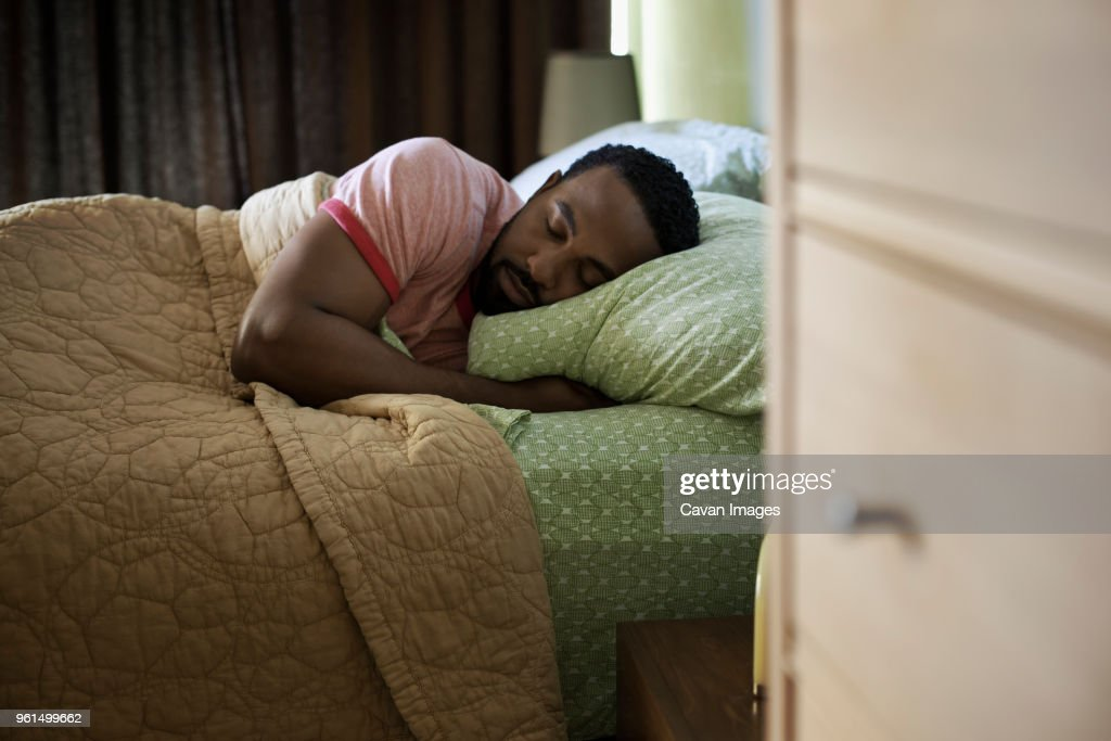Man sleeping on bed at home : Stock-Foto