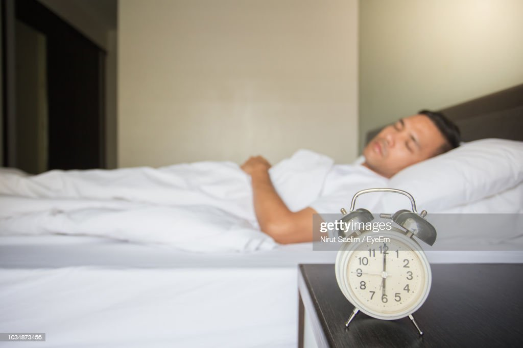 Man Sleeping On Bed By Alarm Clock At Night Table In Bedroom