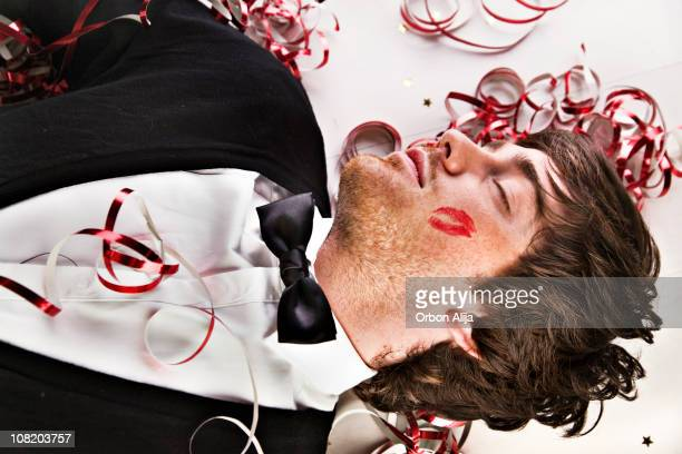 man sleeping on floor at party with cheek lipstick print - gigolo stock photos and pictures