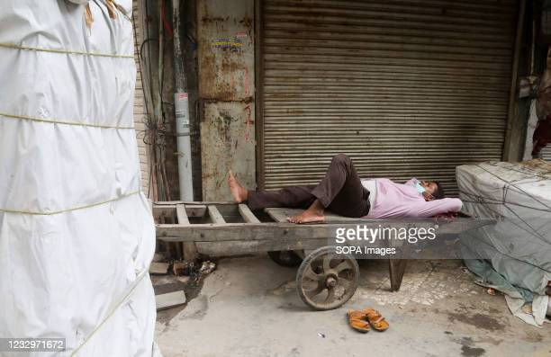Man sleeping on his hand cart in front of a closed shop at Chandani Chowk main market during the lockdown in Old Delhi Chandani Chowk is busy...
