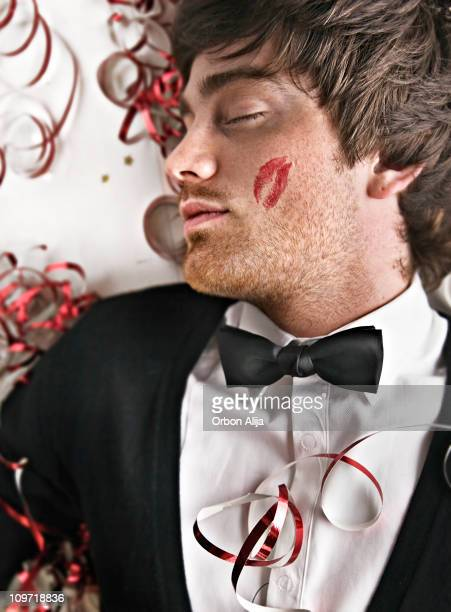 man sleeping on party floor with cheek lipstick kiss - gigolo stock photos and pictures