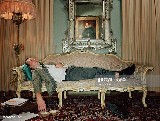 man sleeping on sofa, paperwork on floor - dormir humour photos et images de collection