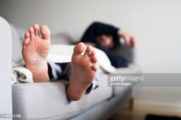 man sleeping on sofa - barefoot stock pictures, royalty-free photos & images