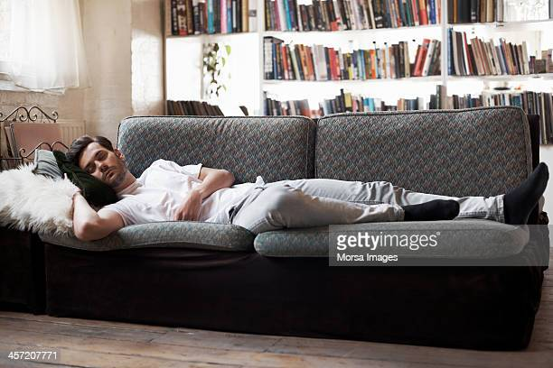 man sleeping on sofa - sofa stock pictures, royalty-free photos & images