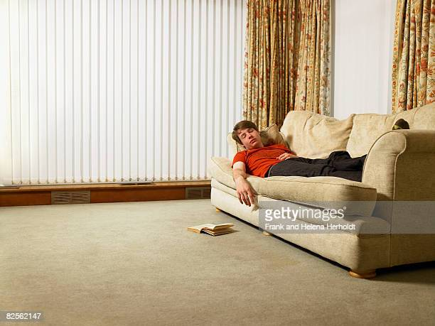 man sleeping on sofa - laziness stock pictures, royalty-free photos & images