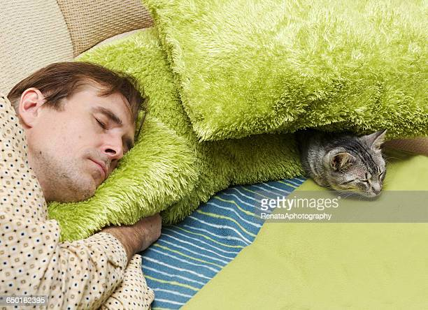Man sleeping on sofa with cat