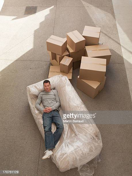 man sleeping on sofa wrapped in plastic - man wrapped in plastic stock pictures, royalty-free photos & images