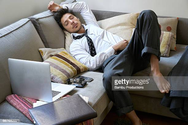 man sleeping on the couch exhausted - laziness stock pictures, royalty-free photos & images