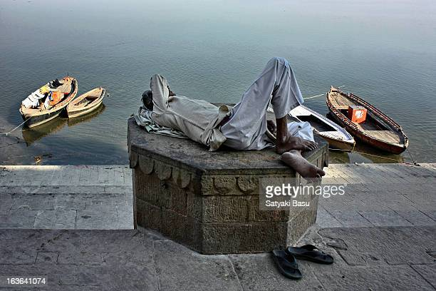 Man sleeping on the ghats of Varanasi in a warm afternoon