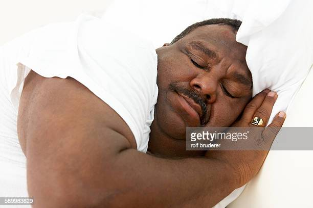 man sleeping - fat black man stock photos and pictures