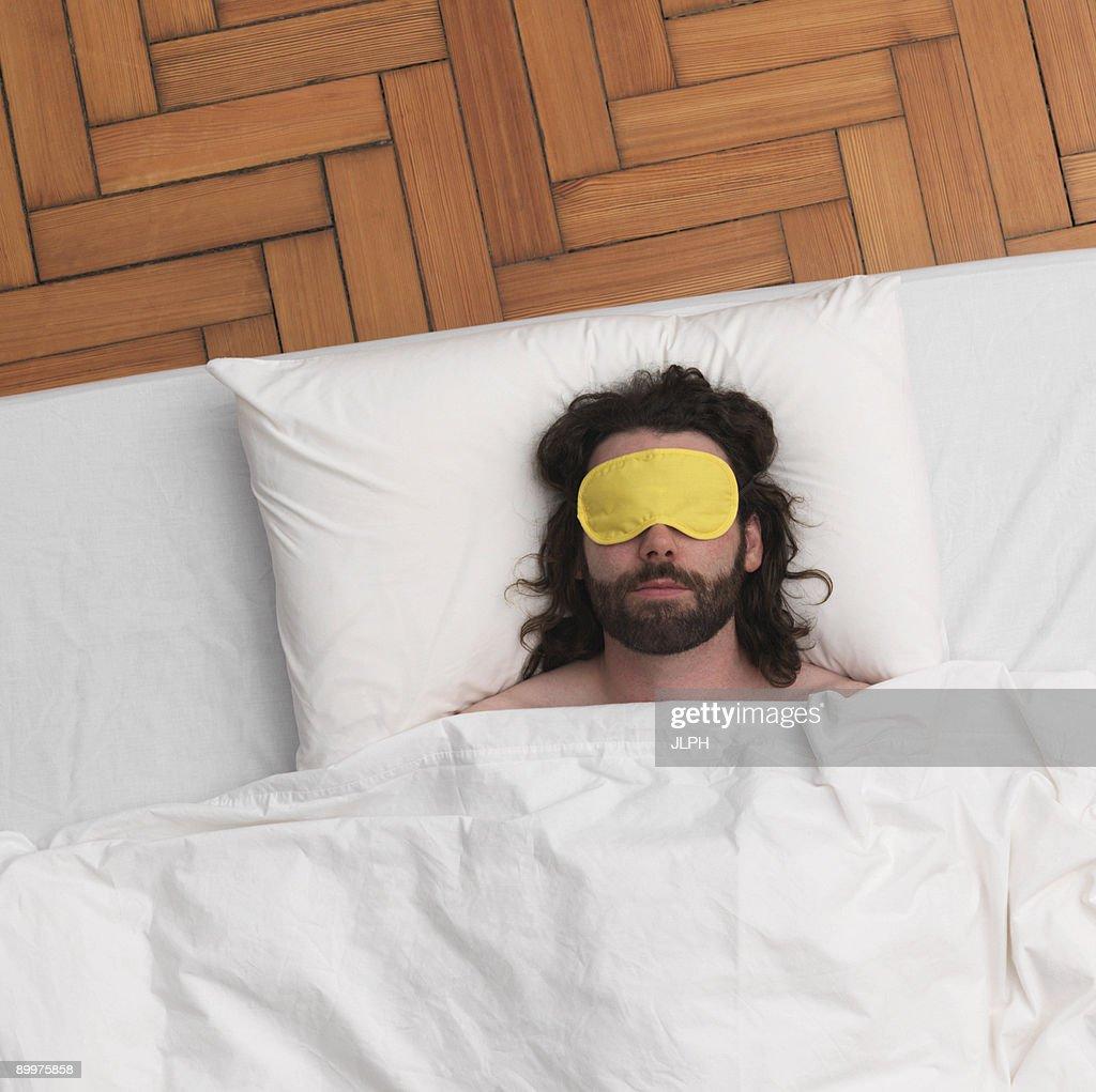 Man sleeping, wearing eye-mask : Foto stock