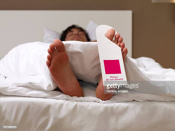 man sleeping with a do not disturb sign on his toe. - dormir humour photos et images de collection