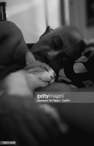 Man Sleeping With Cat On Bed At Home