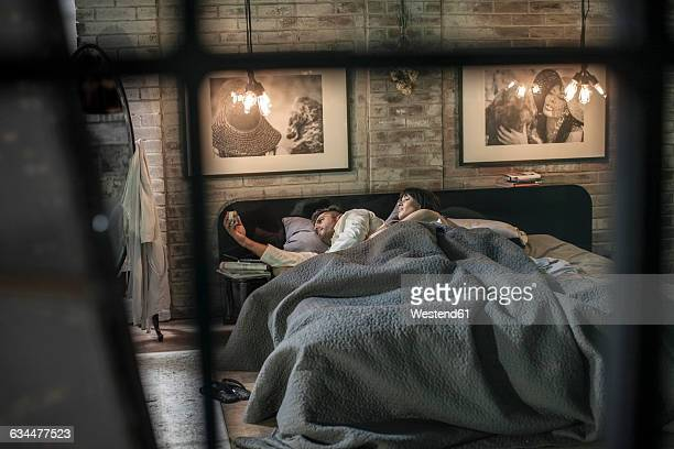 man sleepless in bed looking at alarm clock with wife lying beside him - couple sleeping stock pictures, royalty-free photos & images