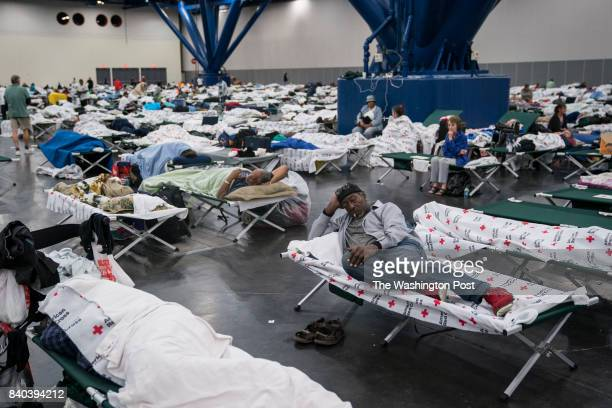 A man sleeps as people seek shelter at the George R Brown Convention Center in Houston TX on Monday Aug 28 2017 Rising water from Hurricane now...